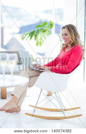 Side view of woman using laptop on rocking chair at home
