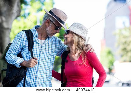Smiling mature couple looking at each other in city