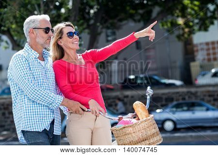 Mature woman pointing while riding bicycle with man on city street