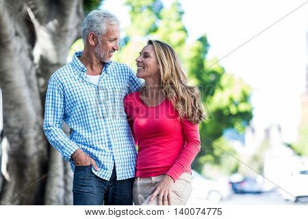 Front view of romantic mature couple standing against tree in city