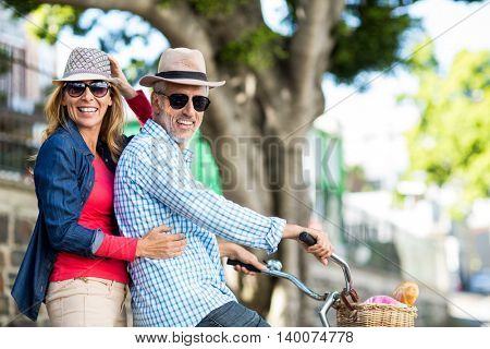 Portrait of mature couple riding bicycle in city
