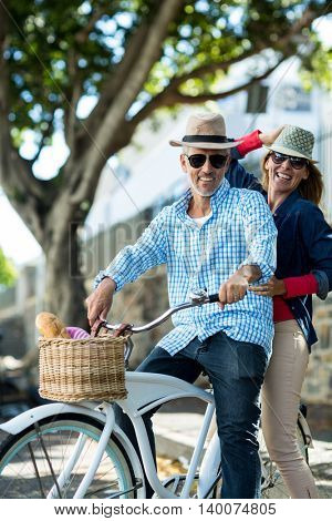 Portrait of mature couple riding bicycle by tree in city