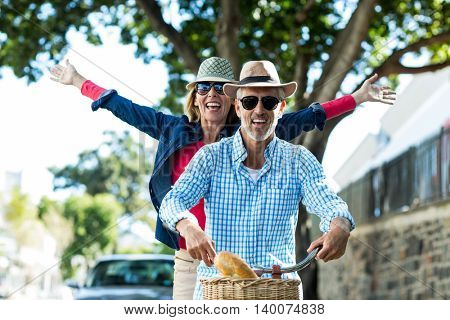 Mature couple enjoying while riding bicycle in city