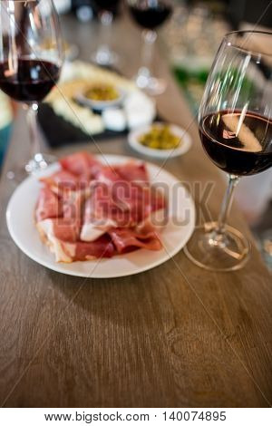 High angle view of meat and wineglass on table at bar