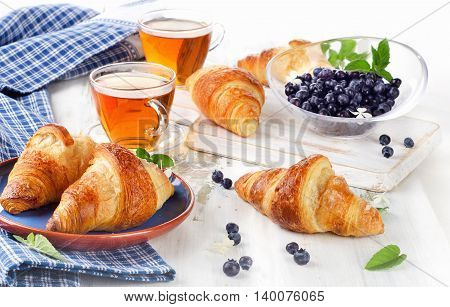 Fresh Croissants With Two Cups Of Black Tea For A Breakfast.