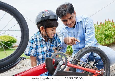 Indian kid learning how his bicycle works