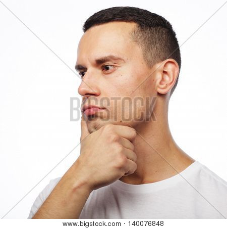 Portrait of handsome young thoughtful man isolated over white ba