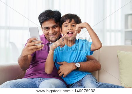 Indian father and son taking funny photos on the pone