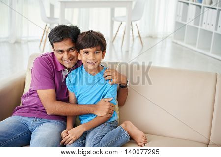 Happy Indian man hugging his preteen son