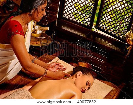 Young woman having Ayurveda spa treatment. Massage in Indian spa salon. Exotic massage.