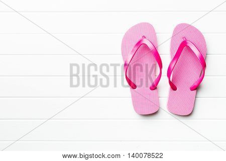 Pink flop flops on white floor.