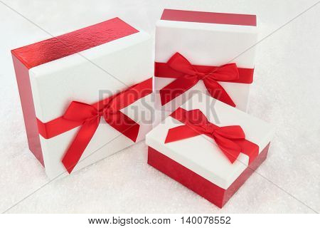 Christmas white glitter gift boxes with red bows on snow background.