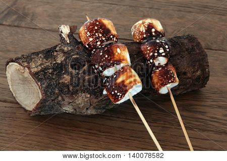 Toasted marshmallows on wooden sticks on an old log over oak wood background.