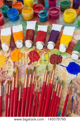 Watercolor paints, brushes and palette on the colorful background. The workplace of the artist. Banner for school