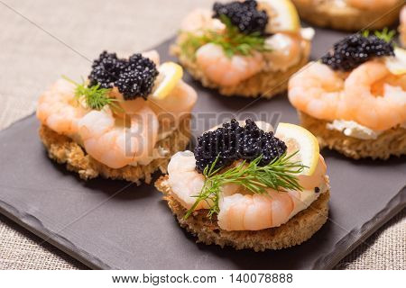 Shrimp Appetizer served on toasted bread and served on a slate plate