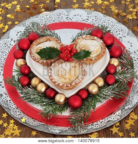 Traditional christmas mince pie cakes with red and gold bauble decorations, holly with snow covered winter greenery and stars on oak background.
