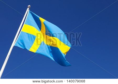 Waving on wind Swedish flag over deep blue sky background