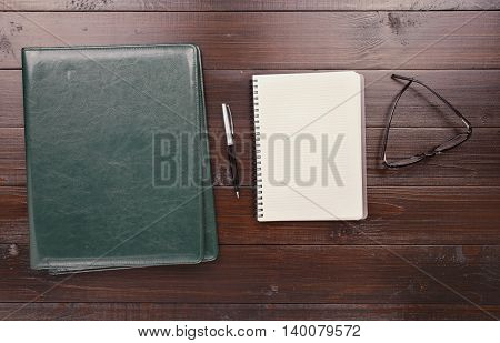 On the Office Desk Is Open Notebook With Blank Pages Pen Leather Business Folder And Glasses. Top view