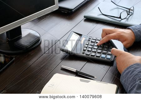 Man Counting Profit Sitting At The Office Desk. Business Background