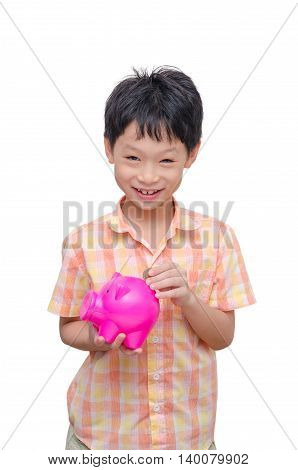 Happy Asian boy inserting coin into piggy bank