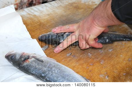 Hands The Fishmonger At The Seafood Market During Cleaning