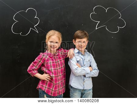 two little smiling children  with phrase clouds drawn on the blackboard