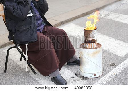 Poor Friar With Brown Robe Warms Up In Front Of The Bonfire In A