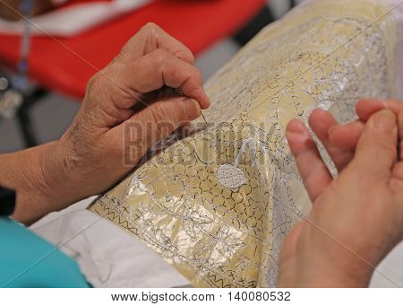 Hands Of The Elderly While Embroidering A Lace With Lace Pillow