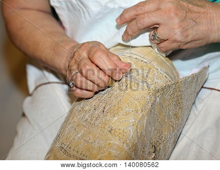 Elderly While Embroidering A Lace With Lace Pillow In Italy