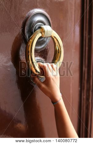 Hand Of Young Girl Knocks On The Door With The Big Brass Handle