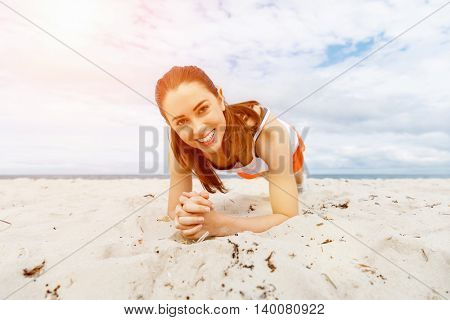 Young woman training on beach outside