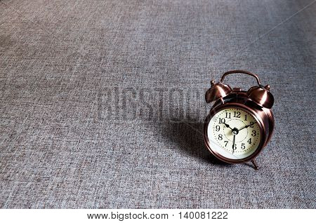 Bronze metalic retro style alarm clock on gray textile surface cushion.