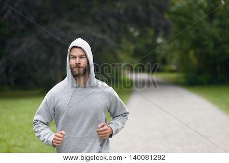 Young Man Jogging Through A Park