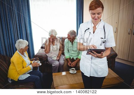 Portrait of a smiling nurse looking at notebook with seniors