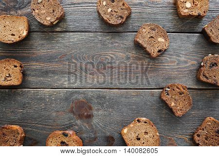 Sweet rye bread on dark wooden background, copyspace. Dark bruschetta slices with hazelnuts and raisins frame on old rustic table, flat lay, frame