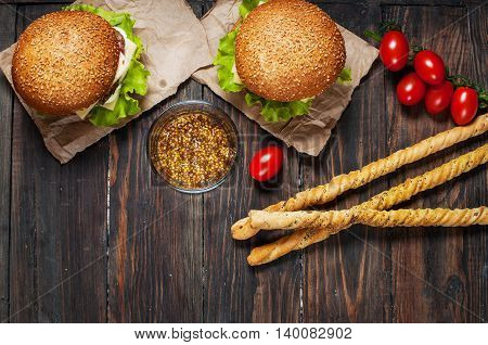 Fresh homemade burgers and breadsticks on wooden background.