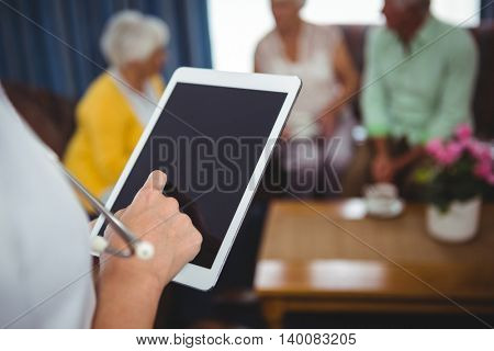 Close-up of a nurse holding a digital tablet in a retirement home