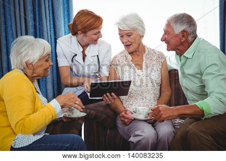 Nurse pointing and showing the screen of a digital tablet to retired person in a retirement home
