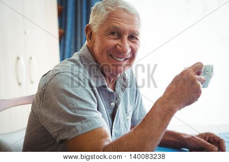 Retired smiling man holding a cup of tea at home
