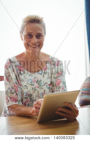 Portrait of senior woman looking at the camera using a digital tablet
