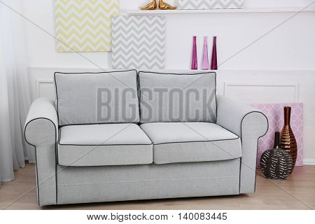 Modern interior with sofa and pictures on shelves in room
