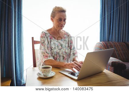 Portrait of concentrated senior woman using a laptop beside a cup of coffee