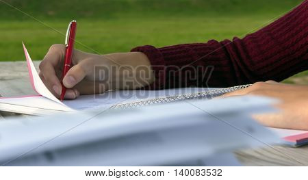 girl sits at a large wooden table and writes in a notebook, close the book, which develops wind sheets,