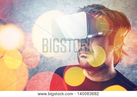 Adult man wearing virtual reality goggles and watching 3D VR multimedia content modern futuristic technology gadget