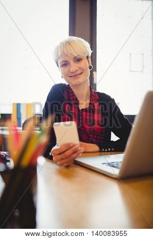 Beautiful young woman using mobile phone at office