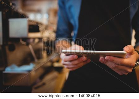 Mid section of man using digital tablet at office cafeteria