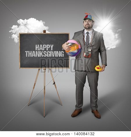 Happy thanksgiving text with holiday gear businessman and blackboard with text