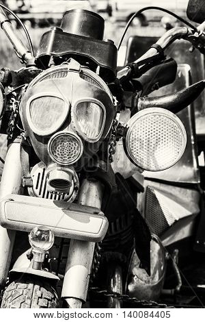 Detail of veteran motorbike with symbolic gas mask. Meeting bikers. Black and white photo. Front view. Handlebars and headlight. Exhibitionism theme.