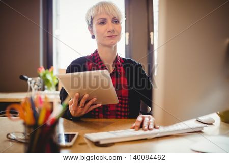Young woman using digital tablet while working on computer at office