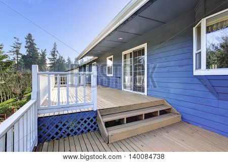 View Of Wooden Walkout Deck With White Railings And Stairs.